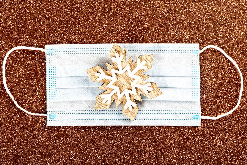 Christmas wooden toy, snowflake and medical mask on brown background, top view