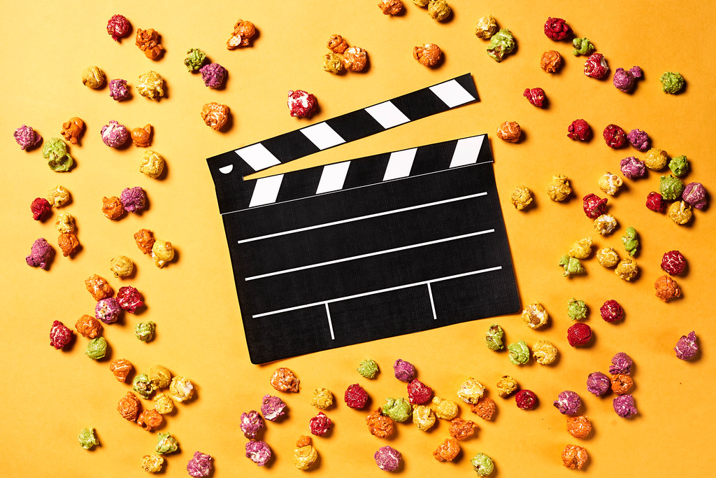 Clapper board with popcorn on yellow background. Cinema concept