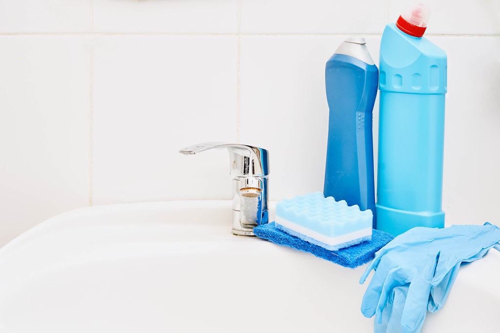 Cleaning supplies on washing basin in modern bathroom