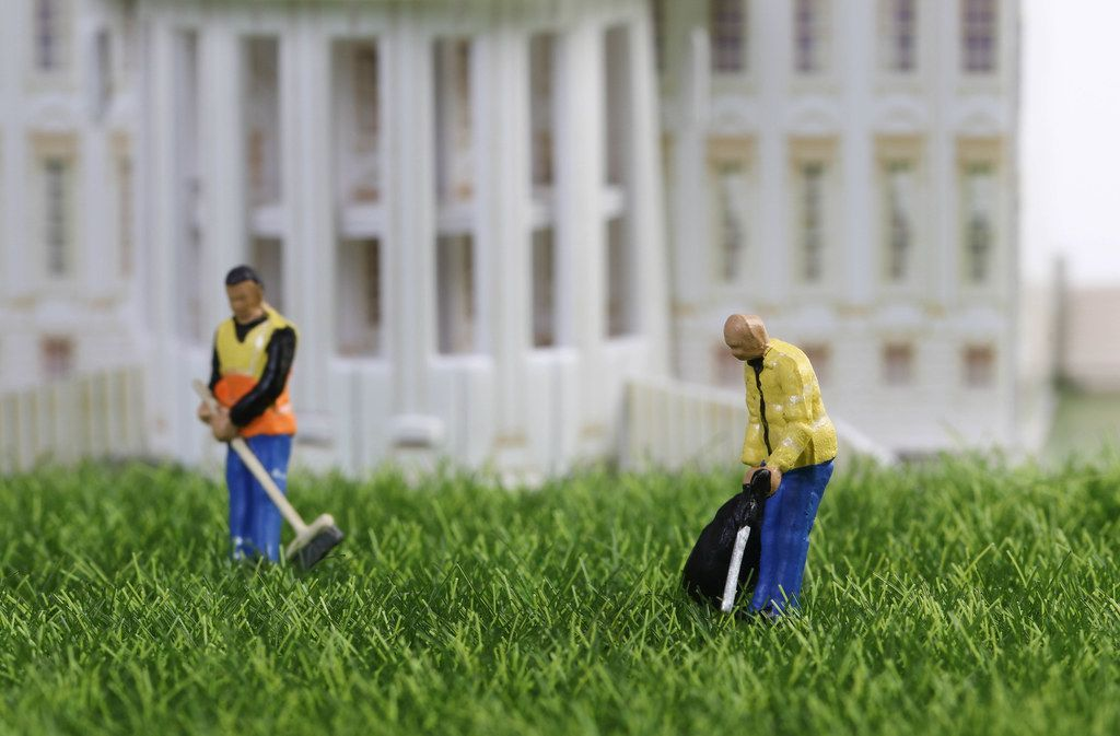 Cleaning workers standing on the grass in front of building