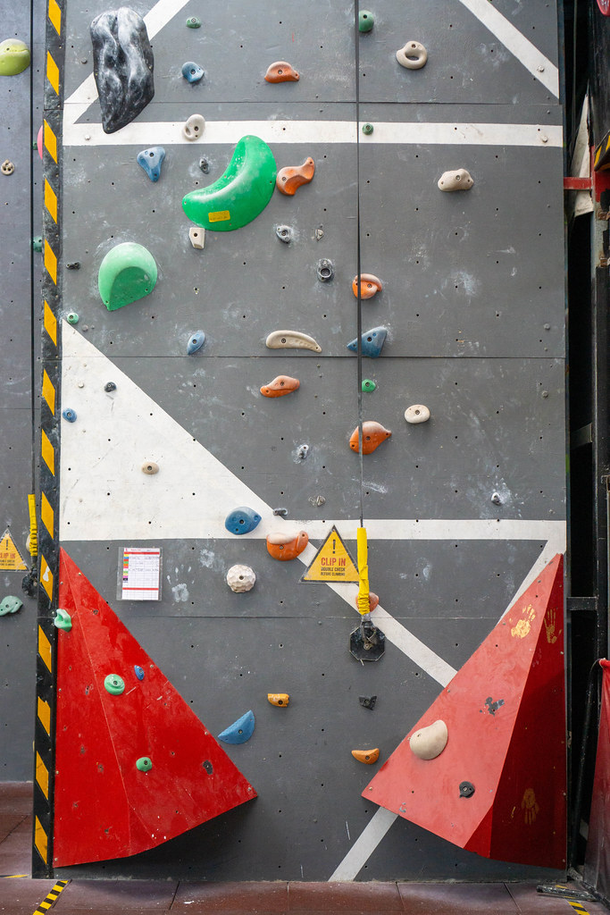 Clip In Warning Sign Before Climbing next to a Rope clipped in an Anchor on a Wall in an Indoor Climbing Hall