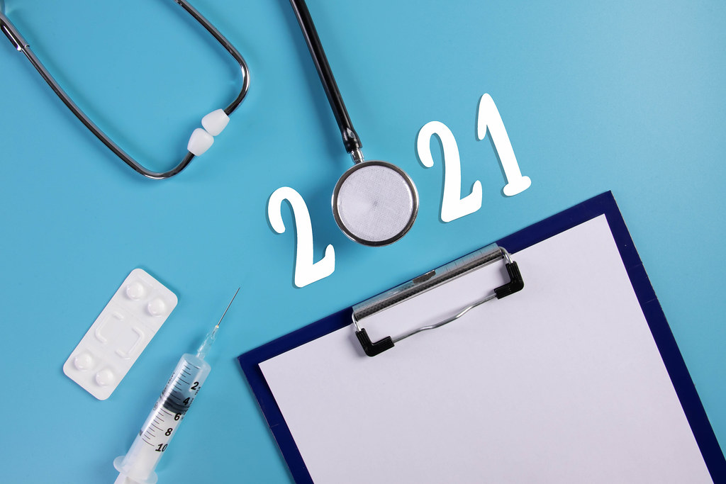 Clipboard, stethoscope, syringe and pills with 2021 text on blue background