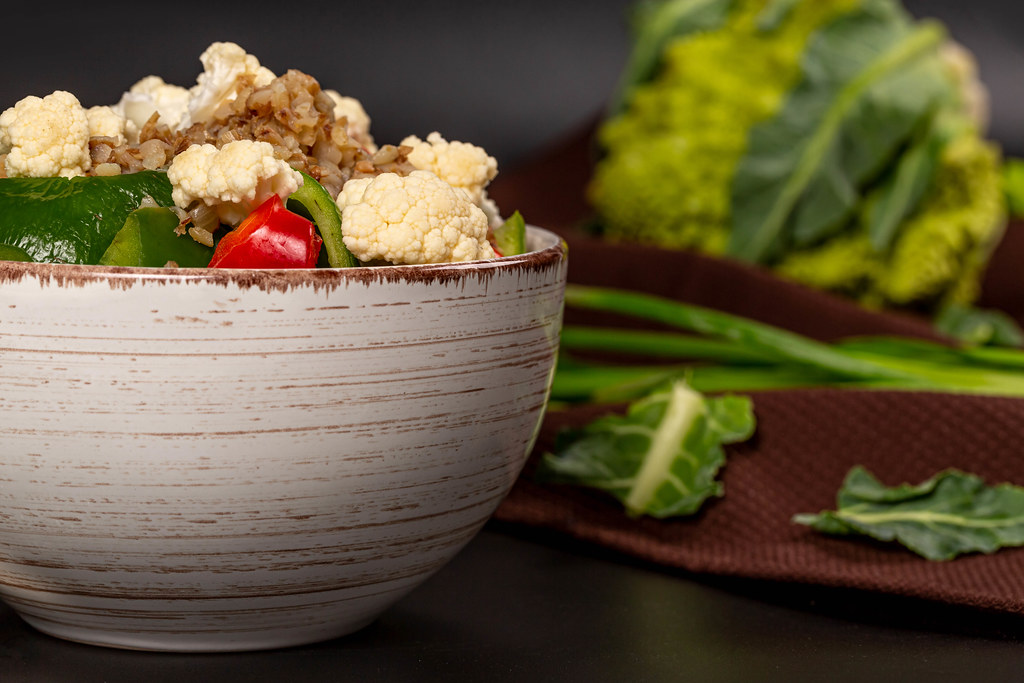 Close-up, a bowl of buckwheat porridge with vegetables on a dark background