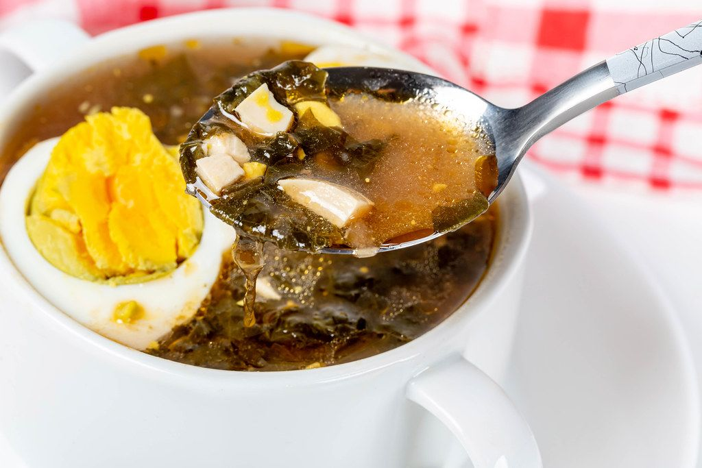 Close-up, a spoon with red soup with eggs and herbs