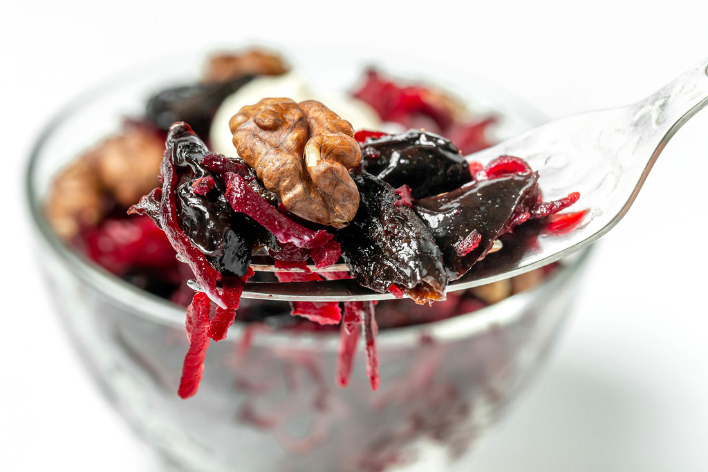 Close up, beetroot salad with walnuts and prunes on fork
