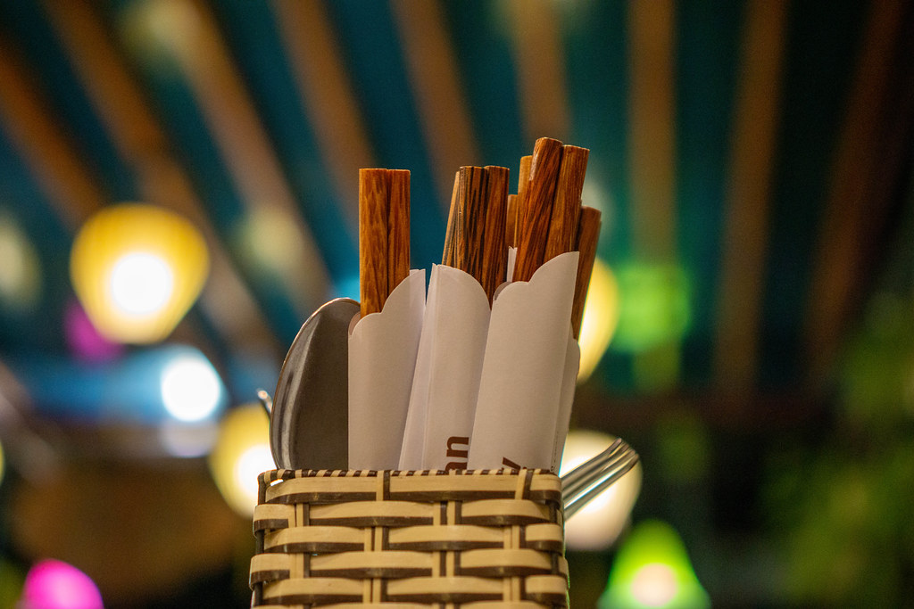 Close Up Bokeh Photo of Cutlery Holder Basket with Spoons, Forks and Wooden Chopsticks in Paper Wrappers in a Restaurant