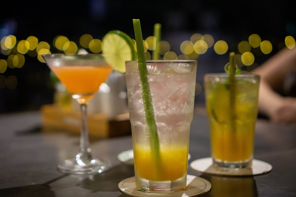 Close Up Bokeh Photo of different Cocktails and Mocktails in Martini and Cocktail Glasses with Ice Cubes and Lemongrass Straws on a Rooftop Bar with Lights in the Background