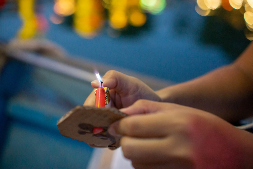 Close Up Bokeh Photo of Person using a Lighter to ignite a Candle of a Floating Paper Lantern in Hoi An, Vietnam
