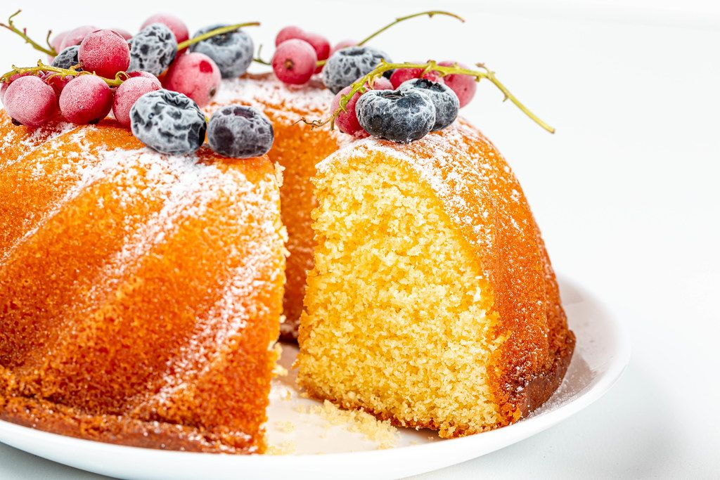 Close-up, cut vanilla muffin with berries and icing sugar