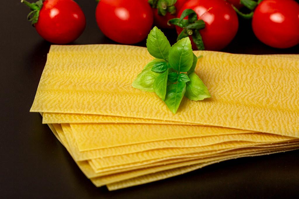 Close-up, dry lasagna sheets with basil and tomatoes
