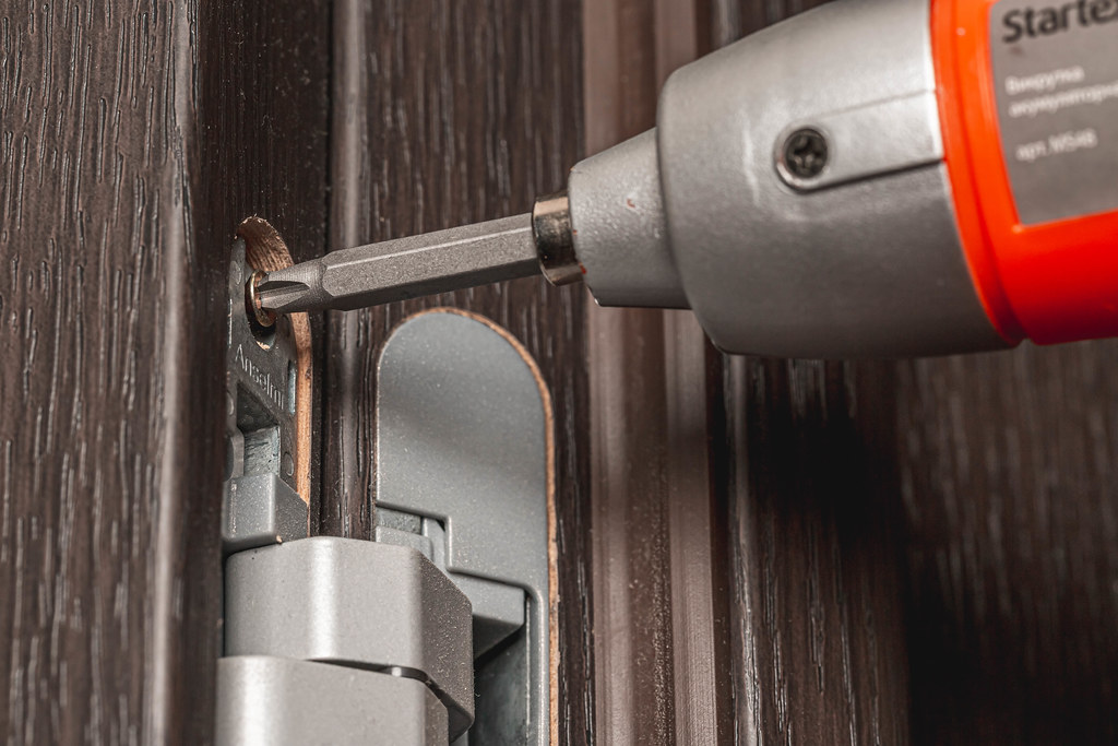 Close-up, electric screwdriver secures the door hinge