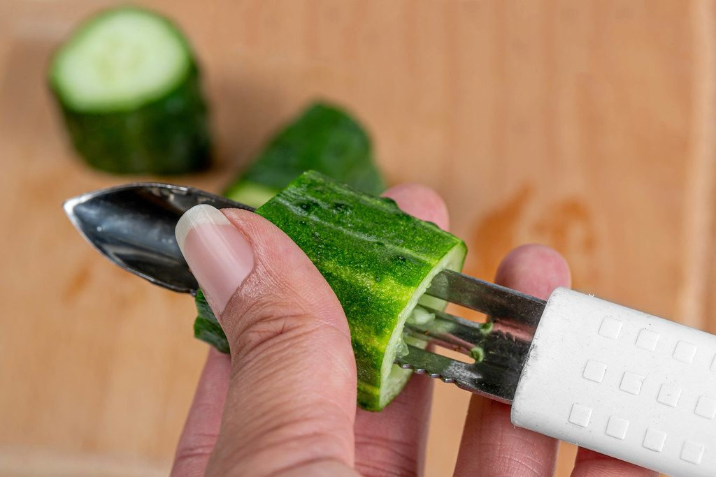 Close-up, female hands cut the pulp from a cucumber