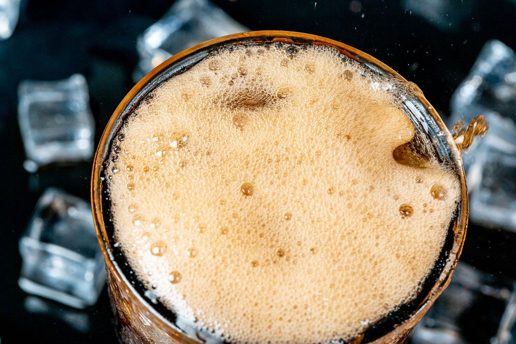 Close-up, foam and bubbles in a glass with cold pepsi