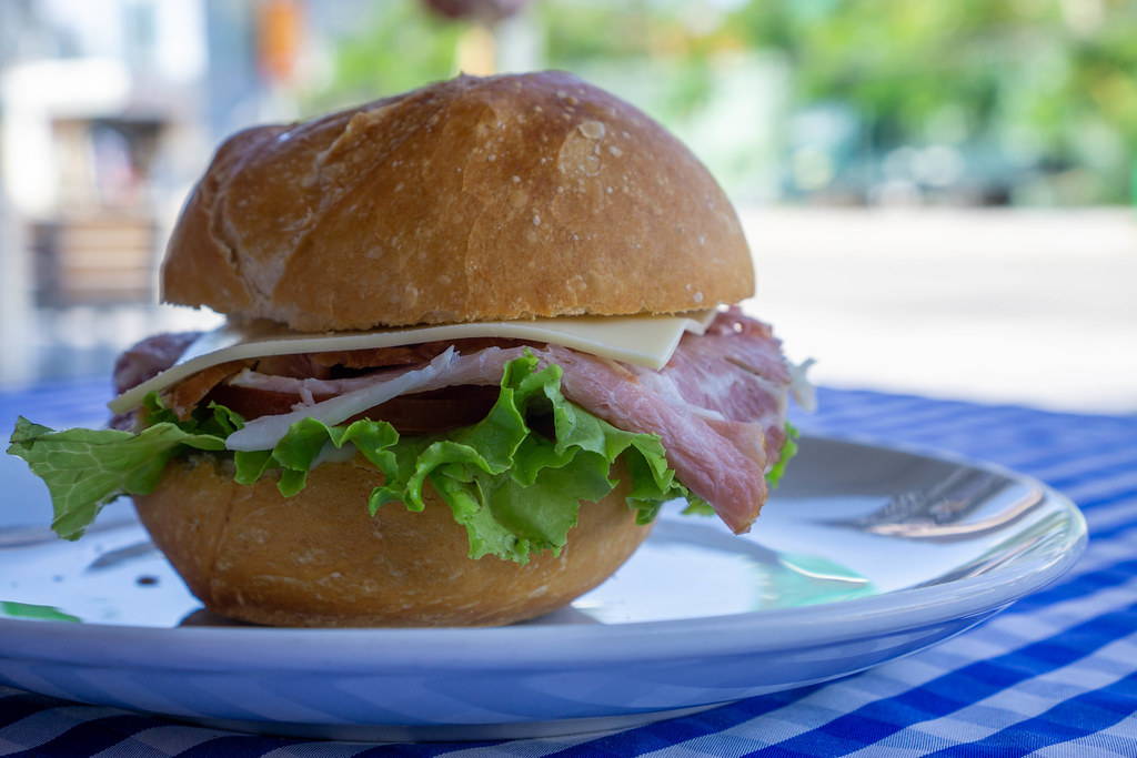 Close Up Food Photo of Bread Roll Sandwich with Cheese, Ham, Tomato, Cucumber, Lettuce and Remoulade Sauce on a White Plate