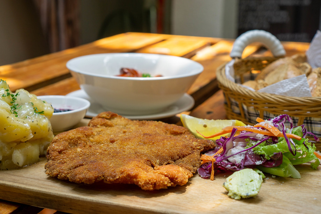 Close Up Food Photo of Chicken Schnitzel with Homemade Potato Salad, Herb Butter, Side Salad and Lemon on a Wooden Table with other German Foods in a Restaurant