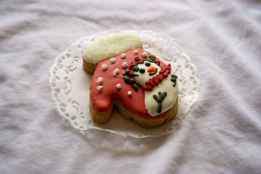 Close Up Food Photo of Christmas Gingerbread Cookie in Gloves Design with Snow as Sugar and Snowman Icing Decoration on Top