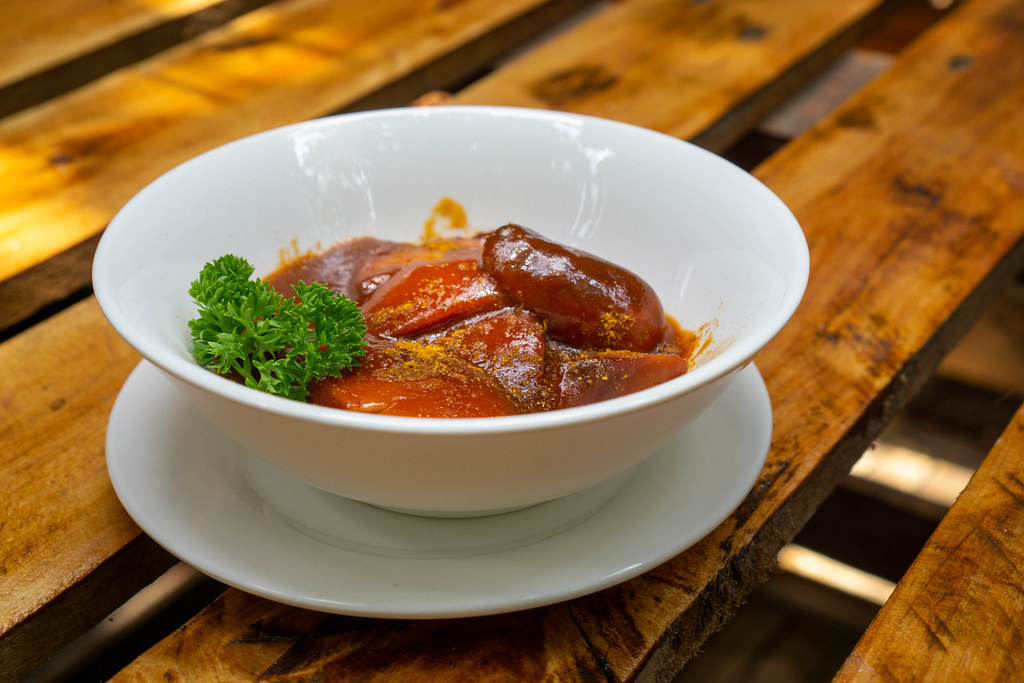Close Up Food Photo of Currywurst with authentic German Bratwurst and homemade Curry Sauce in a White Ceramic Bowl with Curry Powder and Parsley at a German Restaurant