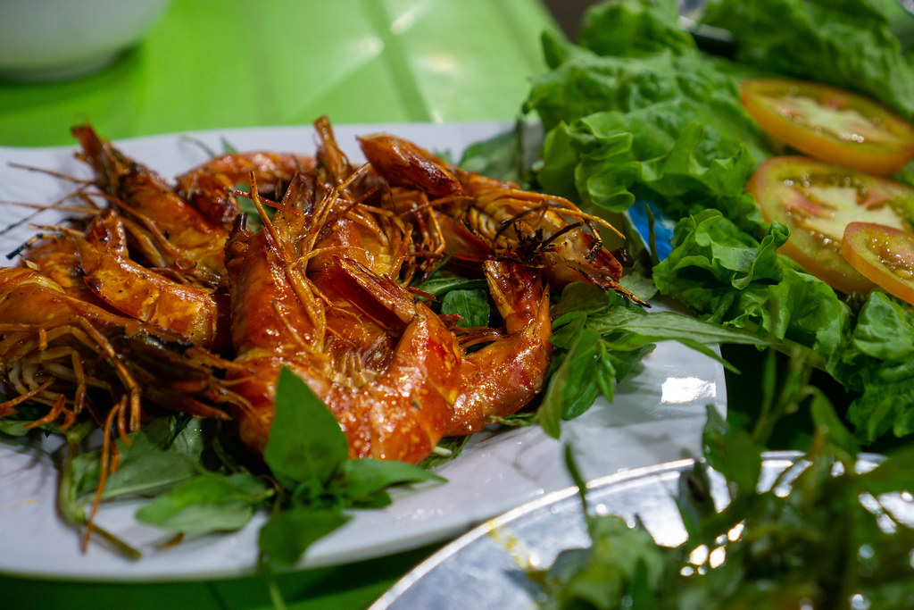 Close Up Food Photo of Grilled Shrimps with Chili and Lemongrass on Herbs at a Street Food Restaurant at a Night Market in Vietnam