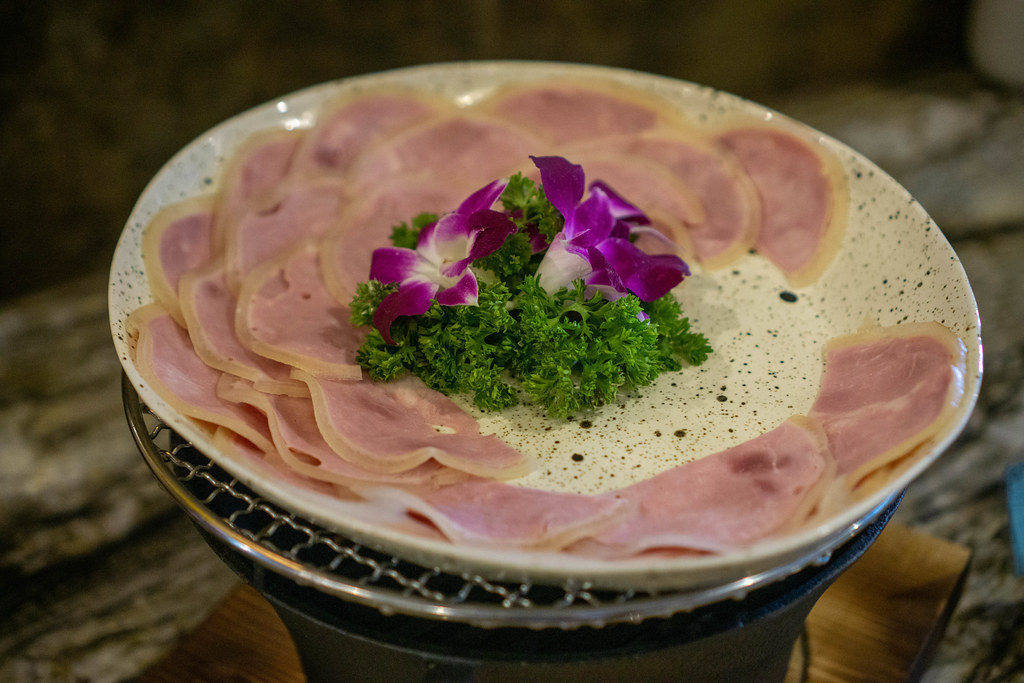 Close Up Food Photo of Ham Cold Cut with Parsley and Flower Decorations on a Plate at a Complimentary Breakfast Buffet at a Hotel