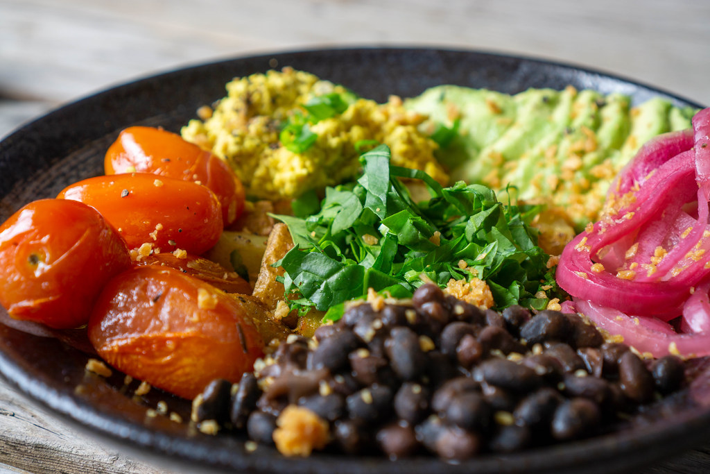 Close Up Food Photo of Healthy Meal with Grilled Cherry Tomatoes, Beans, Scrambled Tofu with Spring Onions, Avocado and Baked Potatoes on a Black Ceramic Plate