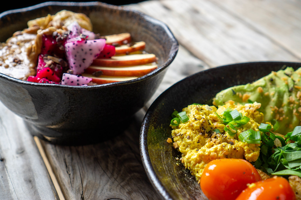 Close Up Food Photo of Healthy Vegan Breakfast with Scrambled Tofu, Cherry Tomatoes and Avocado with Porridge Bowl in the Background on a Wooden Table