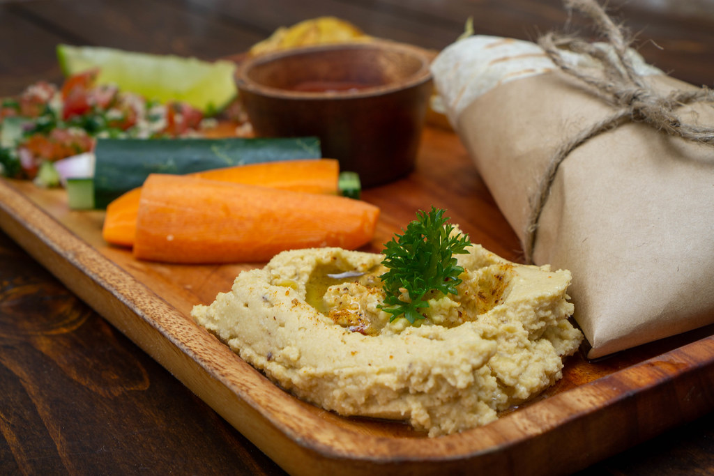 Close Up Food Photo of Homemade Hummus on a Wooden Lunch Plate with Raw Vegetables, Quinoa Toamto Salad and Tortilla Kebab Wrap