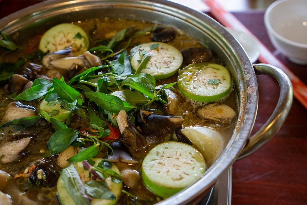 Close Up Food Photo of Hot Pot with Fremented Fish, Mushrooms, Eggplant and Fresh Herbs in a Vietnamese Restaurant