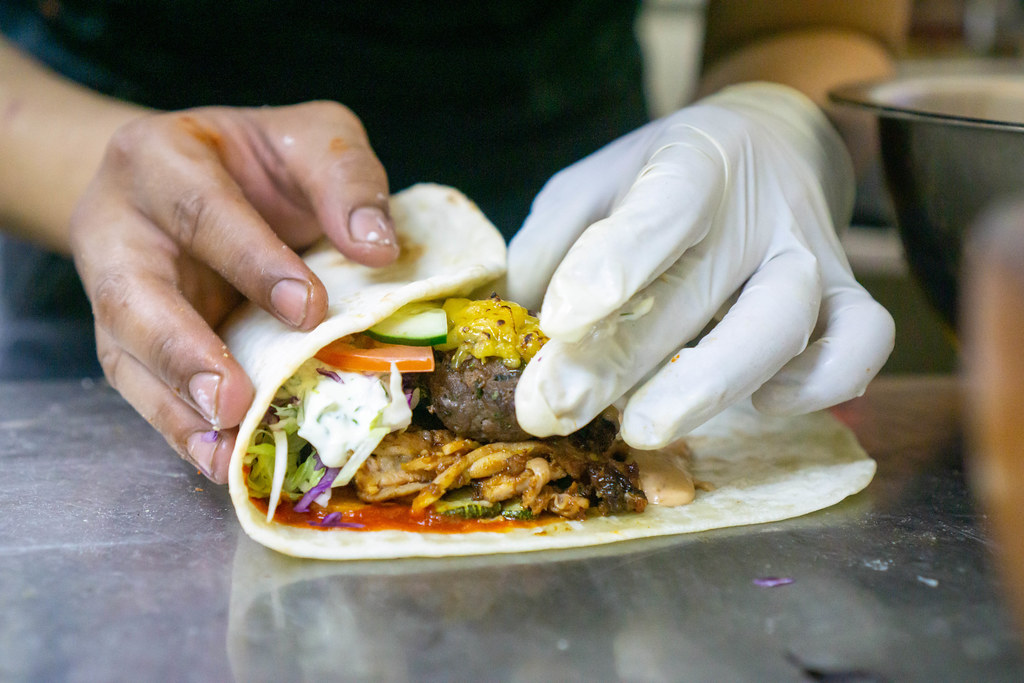 Close Up Food Photo of Kitchen Chef rolling a Doner Durum Kebab Roll with Grilled Lamb, Cheese, Zucchini, Tomatoes, Cucumber, Cabbage, Tzatziki and Cocktail Sauce on a Kitchen Countertop
