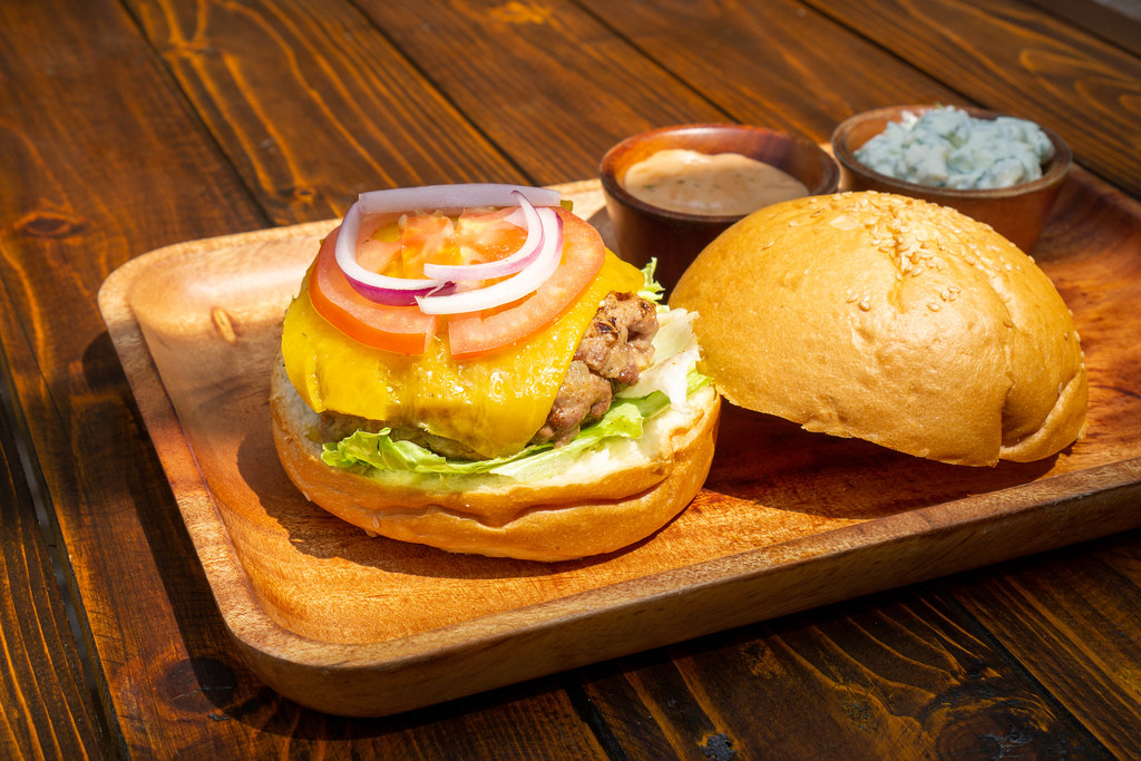 Close Up Food Photo of Kofta Burger with Lamb Meat Patty, Lettuce, Melted Cheese, Tomato, Onion and Sauces on Side on a Wooden Plate in a Restaurant