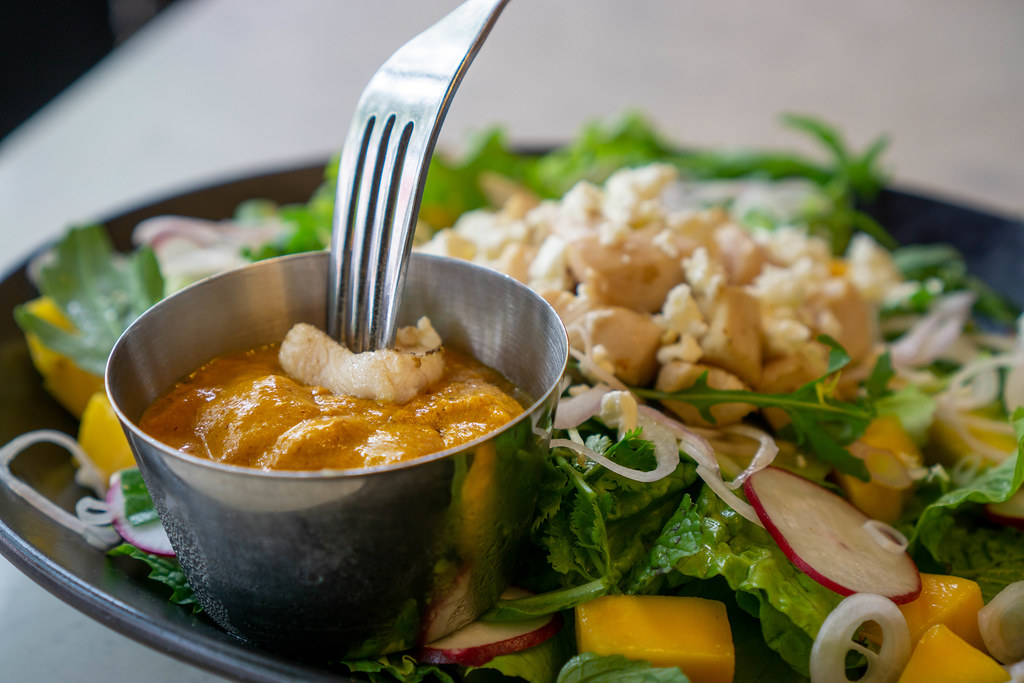 Close Up Food Photo of Mango Curry Chicken Breast with Grilled Chicken Breast on a Fork in a Curry Dip