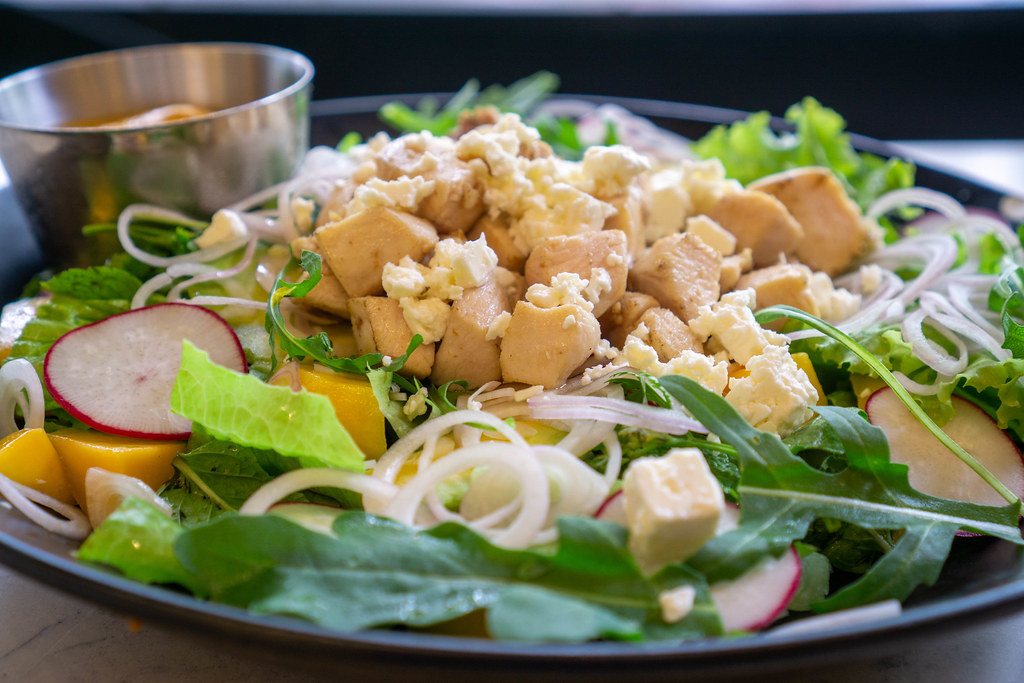 Close Up Food Photo of Mango Curry Chicken Salad with Grilled Chicken Breast, Feta Cheese, Arugula and Onions on a Ceramic Plate