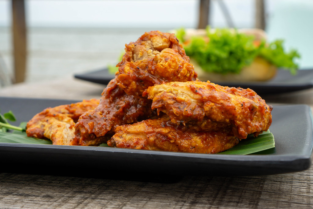Close Up Food Photo of Marinated Spicy Chicken Wings on a Black Plate with a Sandwich in the Background on a Wooden Table
