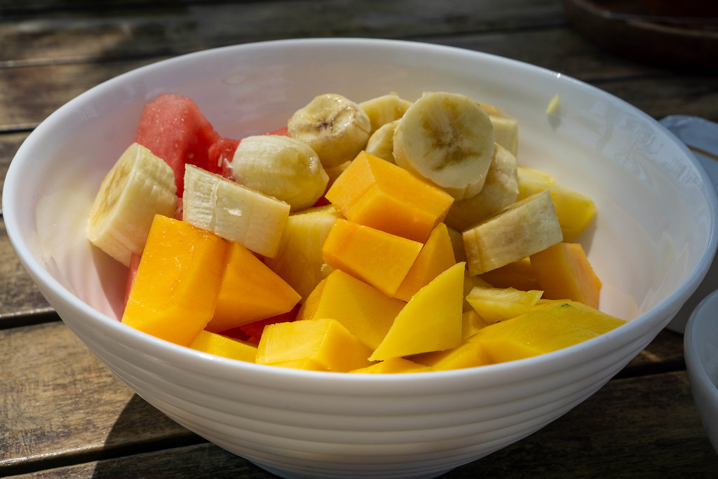 Close Up Food Photo of Mixed Fruit Bowl with sliced Mango, Watermelon, Banana and Pineapple on a Wooden Table in the Sun