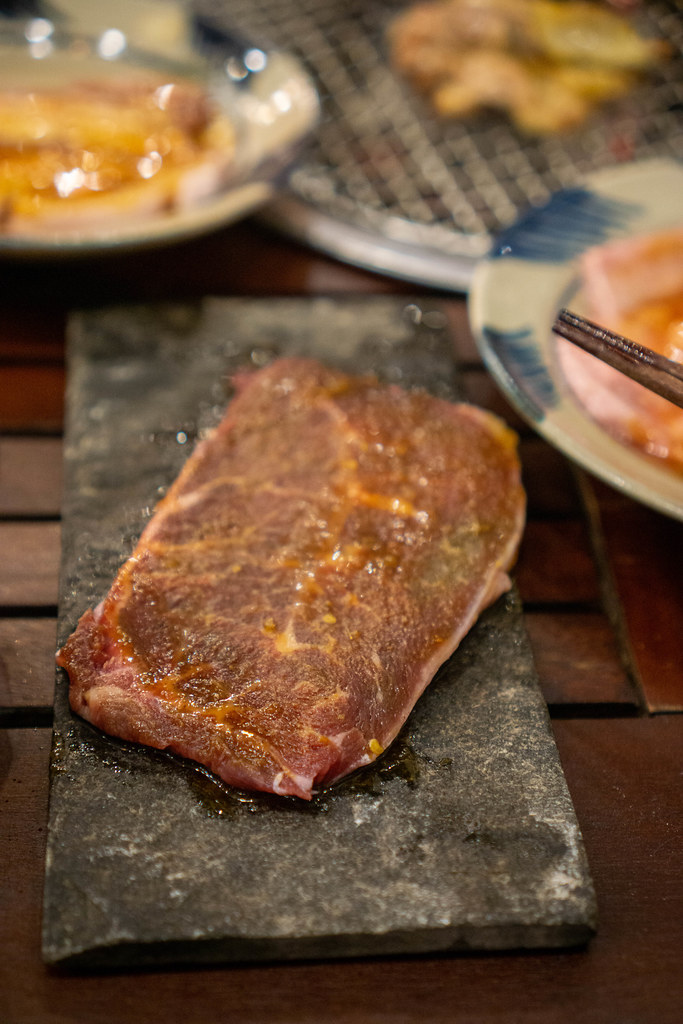 Close Up Food Photo of Raw Beef Steak on a Stone Plate next to a Table Barbecue Grill at a Restaurant