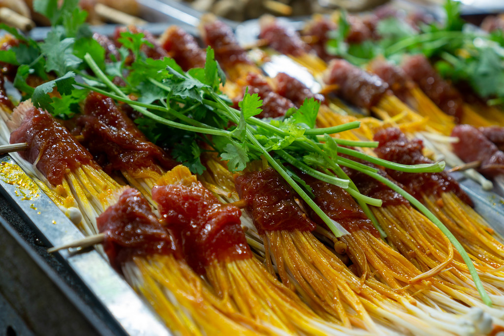 Close Up Food Photo of Skewers of Enoki Mushrooms wrapped in raw and marinated Beef for Barbecue topped with fresh Parsley