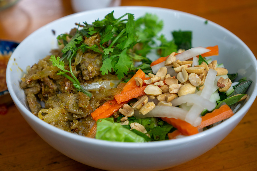 Close Up Food Photo of Vietnamese Dish Bun Thit Xao with Stir Fried Pork, Rice Vermicelli, Pickles, Peanuts and Herbs in a Restaurant