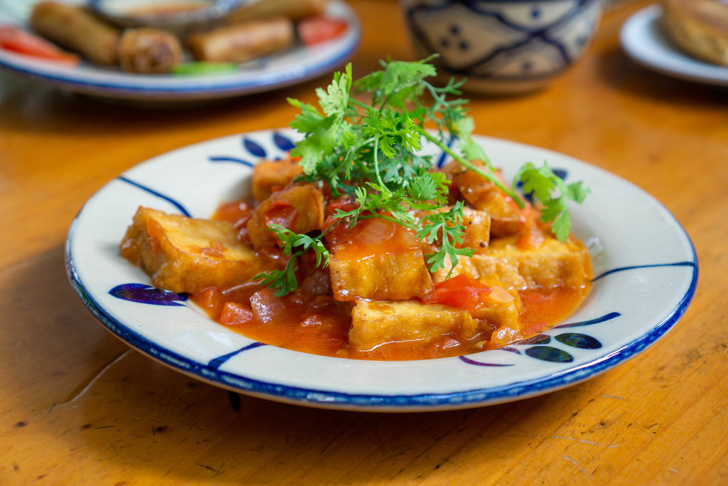 Close Up Food Photo of Vietnamese Dish with Tofu, Tomato Sauce, Parsley and Spices on a Ceramic Plate in a Restaurant