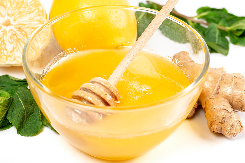 Close-up, fresh honey in a glass bowl on a white background with ginger and mint leaves