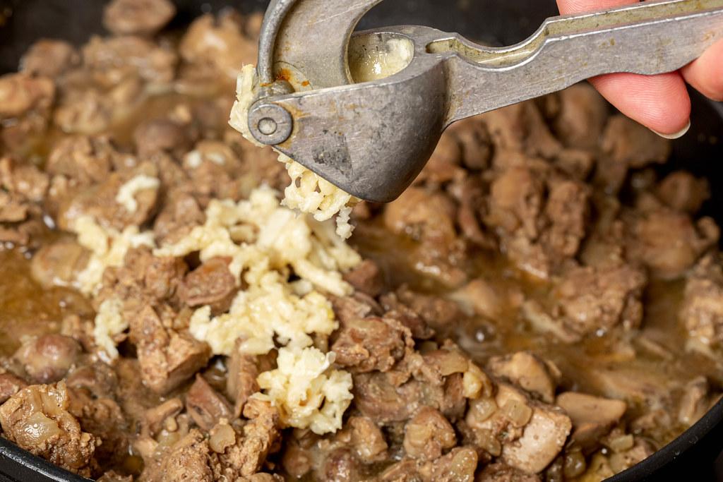Close-up, garlic press chopping garlic