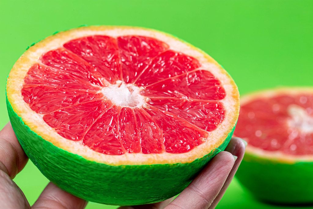 Close-up, half of fresh ripe grapefruit in a female hand