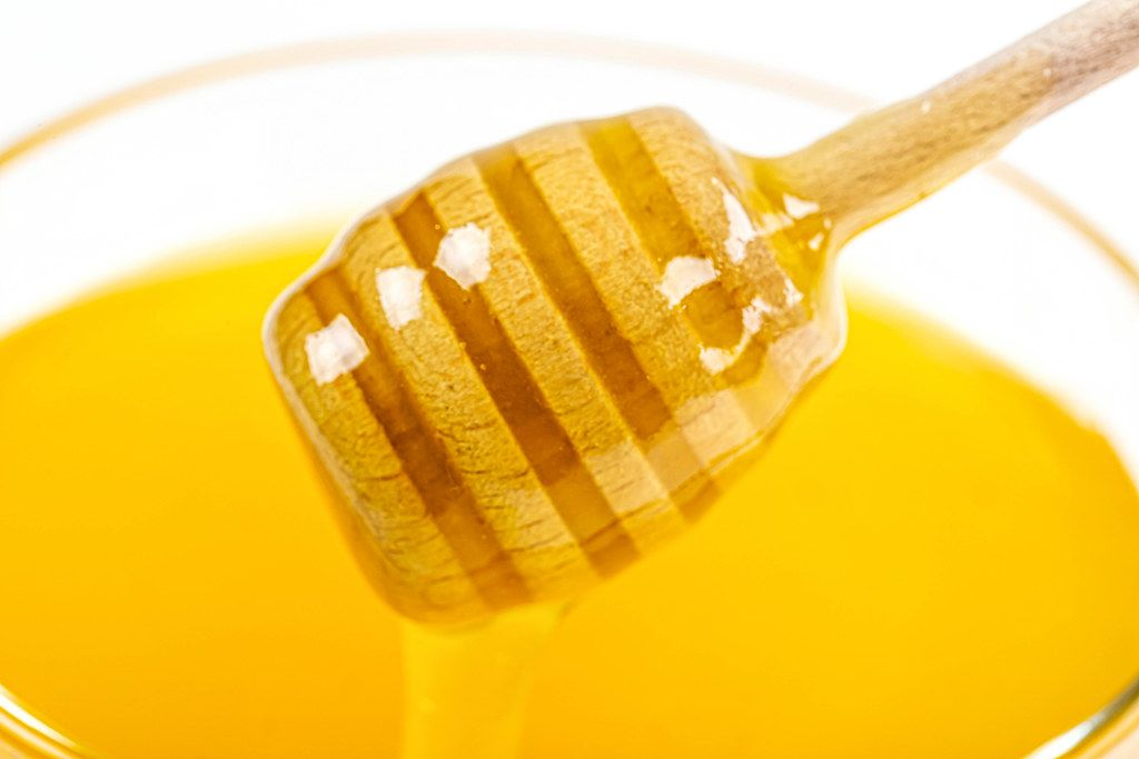 Close-up, honey dipper on the background of fresh bee honey
