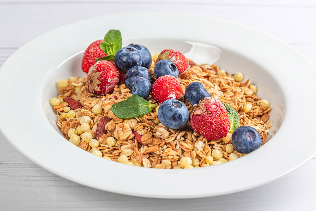 Close-up, multi-cereal breakfast with seeds, dry berries, strawberries and blueberries