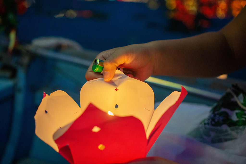 Close Up Night Photo of Person holding a Floating Paper Lantern with a lit up Candle in one Hand with a Lighter in Hoi An, Vietnam