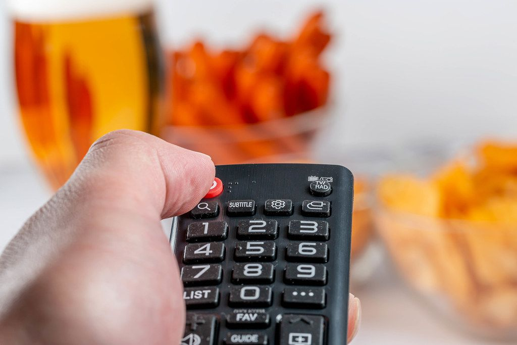 Close-up of a hand with a TV remote against the background of snacks and beer