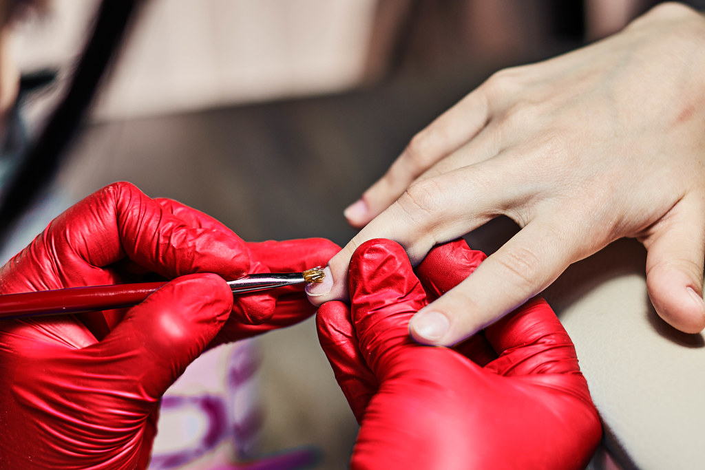 Close-up of beautiful woman hands getting manicure in spa salon