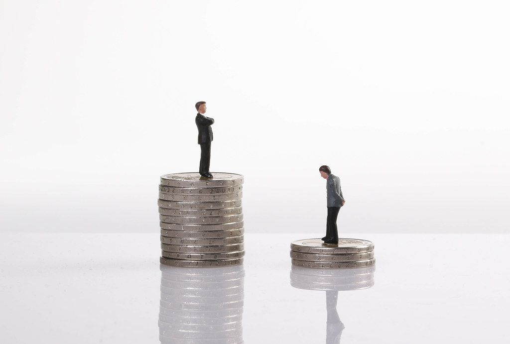 Close up of businessman miniature people figures standing on stack of coins