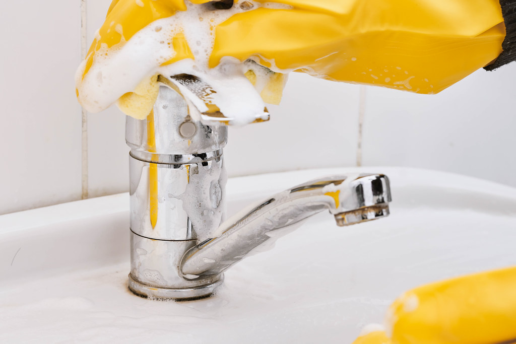 Close-up of female hands with protective gloves scrubbing and cleaning bathroom faucet