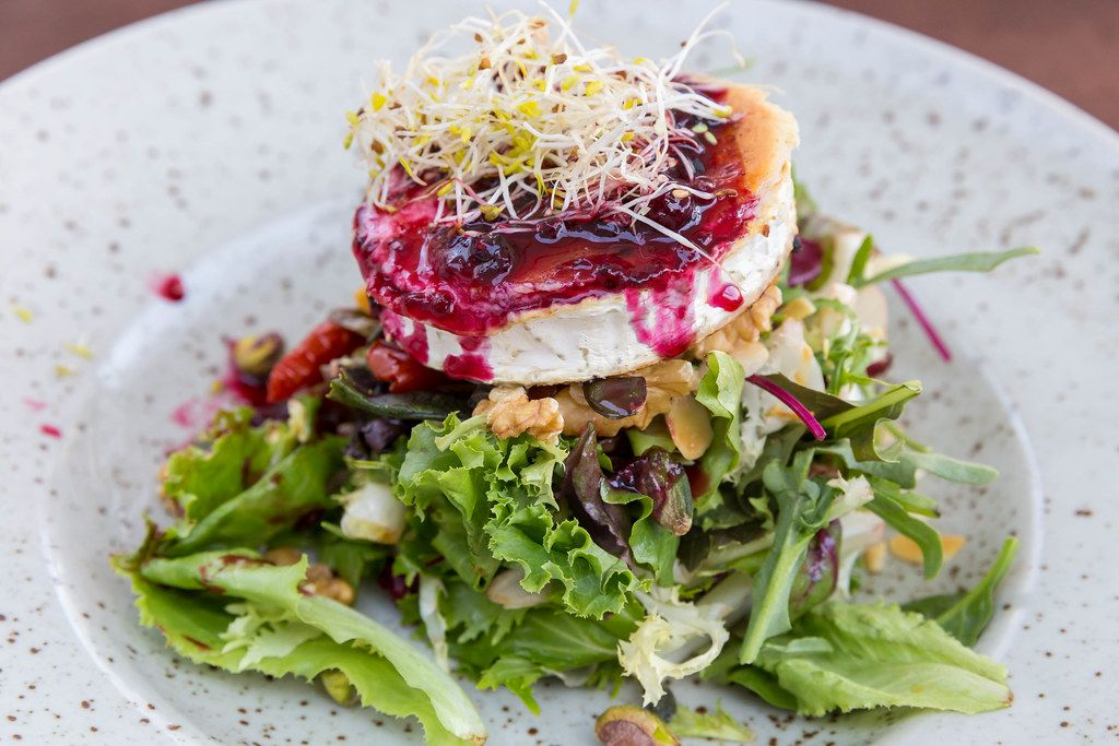 Close-up of grilled goat cheese with salad, sprouts, red berries dressing, walnuts. Q11, Pollença, Majorca