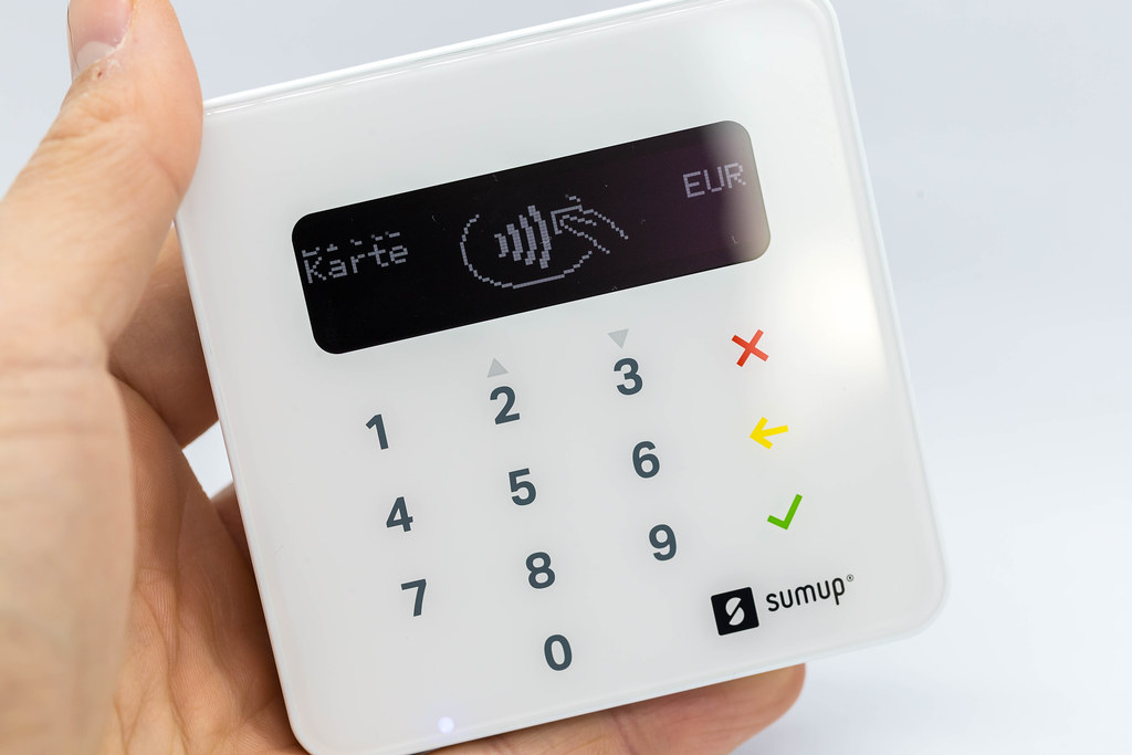 Close-up of hand holding a white SumUp Air Card Reader: portable device for contactless payments