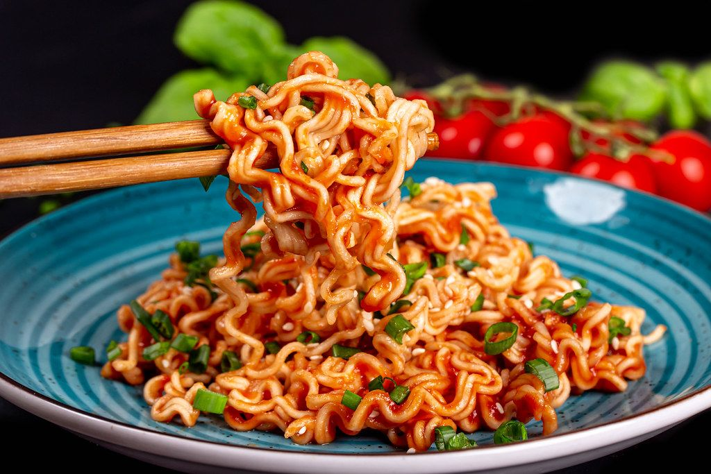 Close up of pasta with tomato sauce on wooden chopsticks